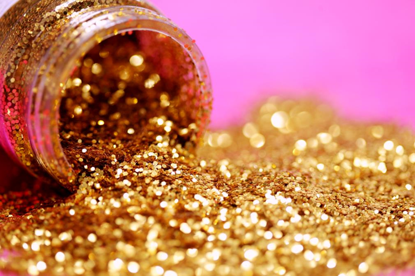 Image of gold glitter spilling out of a jar against a pink background
